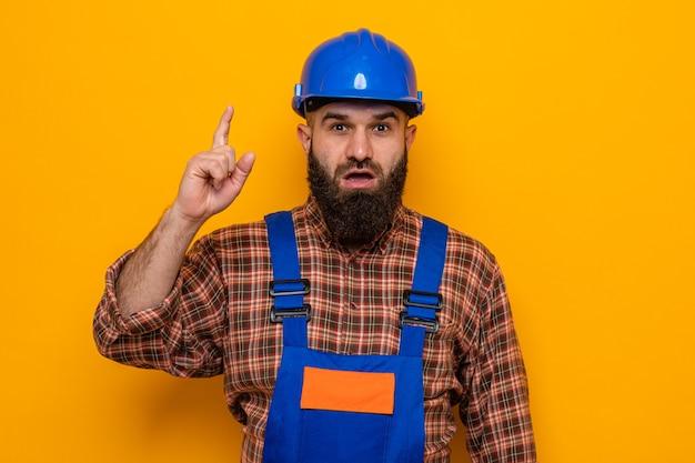 Bärtiger baumeistermann in der bauuniform und im sicherheitshelm, die kamera glücklich und überrascht betrachten zeigefinger, der neue idee über orange hintergrund steht