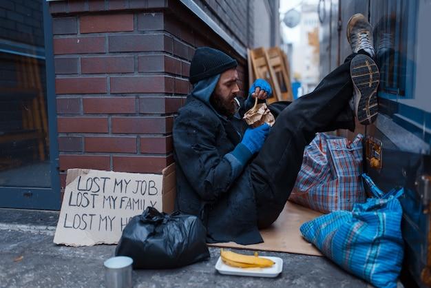 Bärtiger bettler isst burger auf stadtstraße