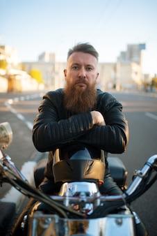 Bärtiger biker auf klassischem hubschrauber, vorderansicht