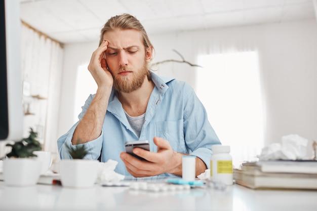 Bärtiger blonder männlicher büroangestellter, der unglücklich auf den bildschirm des smartphones schaut, sich auf seinen ellbogen stützt und während des harten arbeitstages am tisch vor dem bildschirm sitzt. manager leidet unter kopfschmerzen.