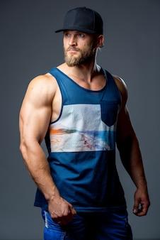 Bärtiger bodybuilder gekleidet in ein trägershirt.