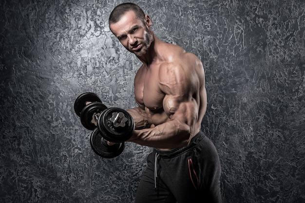 Bärtiger bodybuilder mit dummköpfen