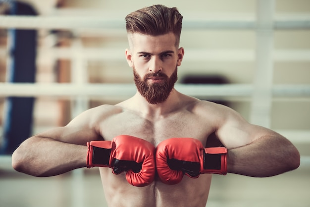 Bärtiger boxer mit dem bloßen torso in den roten boxhandschuhen.