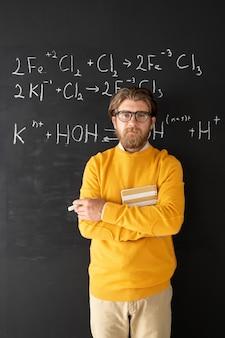 Bärtiger chemielehrer in freizeitkleidung, der auf chemische formel auf tafel zeigt, während smartphone-kamera während online-lektion betrachtet