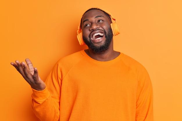 Bärtiger dunkelhäutiger mann hebt handlachen positiv hört audiospur über stereokopfhörer