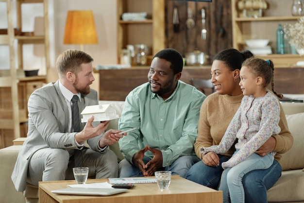 Bärtiger eleganter berater mit modellhaus, das erwachsenes ethnisches paar mit kind auf neuen immobilien berät
