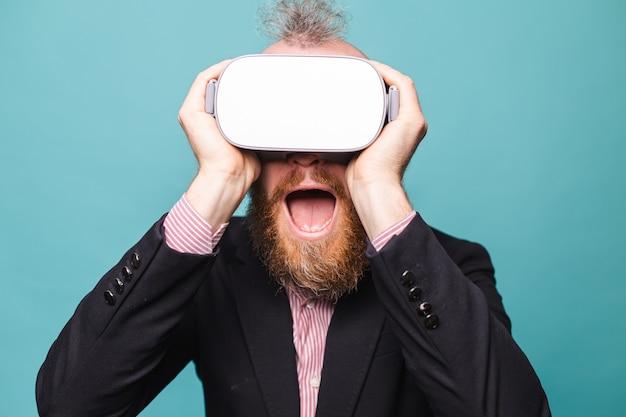 Bärtiger europäischer mann im dunklen anzug lokalisiert, tragen vr brille auf kopf mit aufgeregtem erstauntem schockiertem gesicht offenem mund