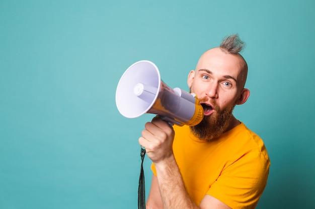 Bärtiger europäischer mann im gelben hemd isoliert, verrücktes geschrei im megaphonlautsprecher, aufmerksamkeit!