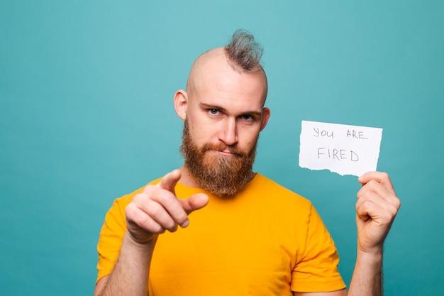 Bärtiger europäischer mann im gelben hemd lokalisiert, das papier mit ihnen hält, ist gefeuerter text, der mit dem finger nach vorne zeigt