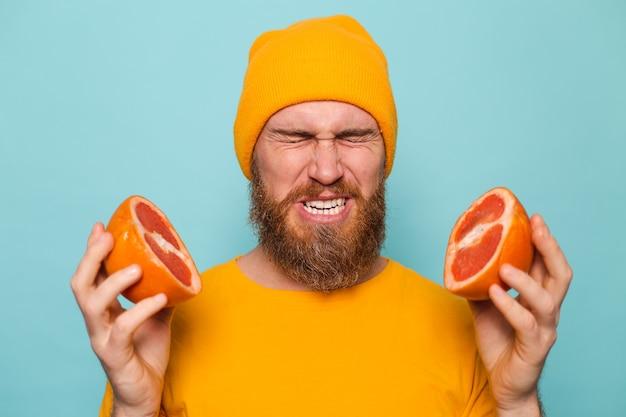 Bärtiger europäischer mann im gelben hemd lokalisiert, grapefruitgeschmack haltend, falten von bitterkeit