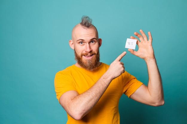 Bärtiger europäischer mann im gelben hemd lokalisiert, hält ja mit überraschung und erstauntem ausdruck aufgeregtem gesicht.