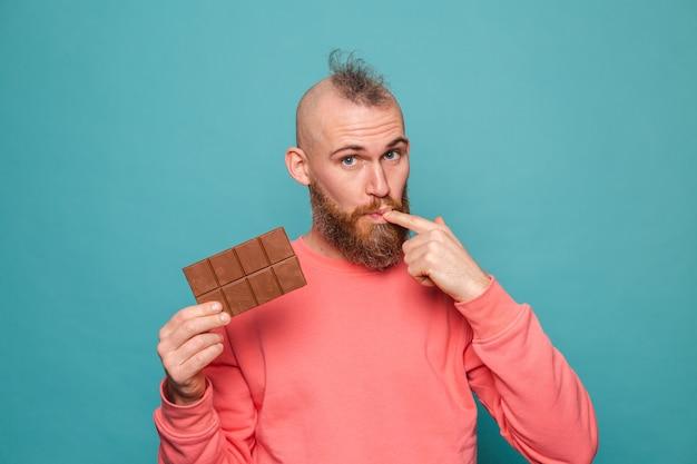 Bärtiger europäischer mann im lässigen pfirsich lokalisiert, der köstliche schokoladenleckfinger hält