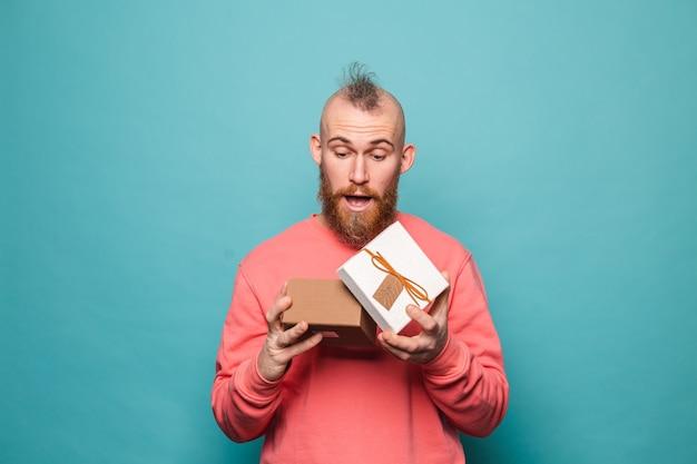 Bärtiger europäischer mann im lässigen pfirsich lokalisierte, aufgeregte eröffnungsgeschenkbox