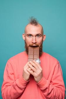 Bärtiger europäischer mann im lässigen pfirsich lokalisierte, beißende schokolade