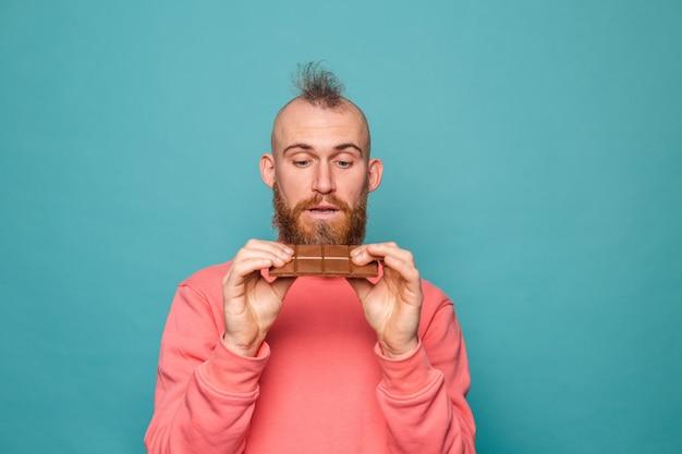 Bärtiger europäischer mann in lässigem pfirsich lokalisiert, der köstliche schokolade hält