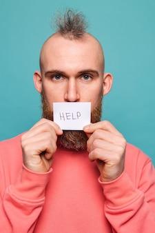 Bärtiger europäischer mann in lässigem pfirsich lokalisiert, papier mit hilfezeichen brutal mit ernstem gesicht haltend