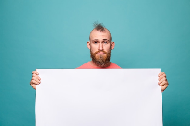 Bärtiger europäischer mann in lässigem pfirsich lokalisiert, weiße leere pappe mit traurigem unglücklichem gesicht haltend