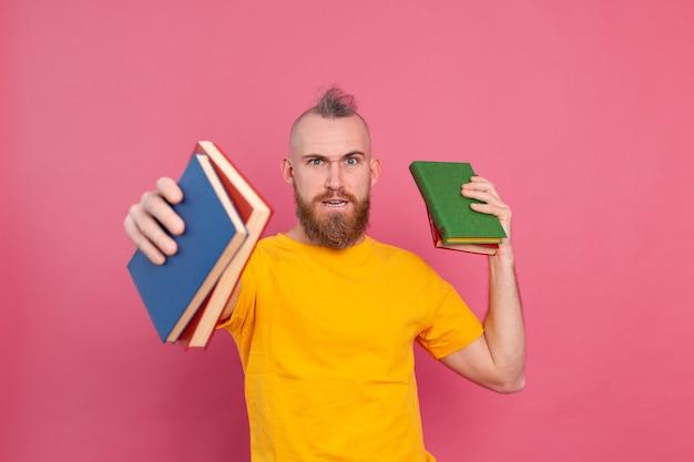 Bärtiger europäischer mann mit stapel bücher auf rosa