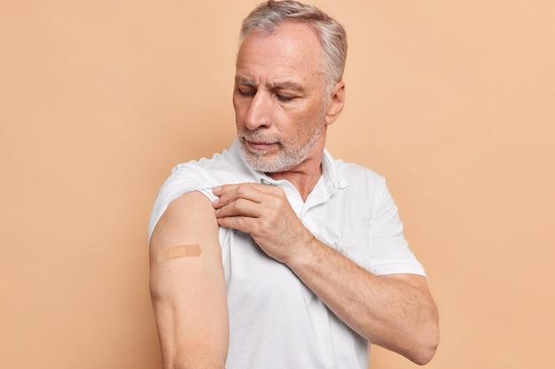 Bärtiger europäischer mann sieht arm mit gips an, der mit coronavirus-impfstoffen zufrieden ist, die sicher und effektiv sind, trägt weißes t-shirt isoliert auf beige wand