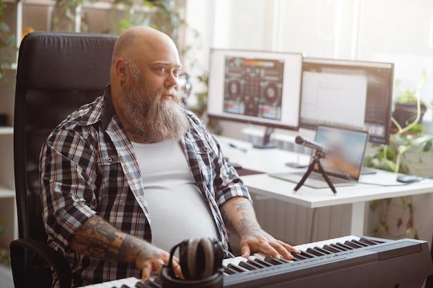 Bärtiger fettleibiger mann spielt sound-synthesizer in der nähe des schreibtisches mit monitoren im heimstudio