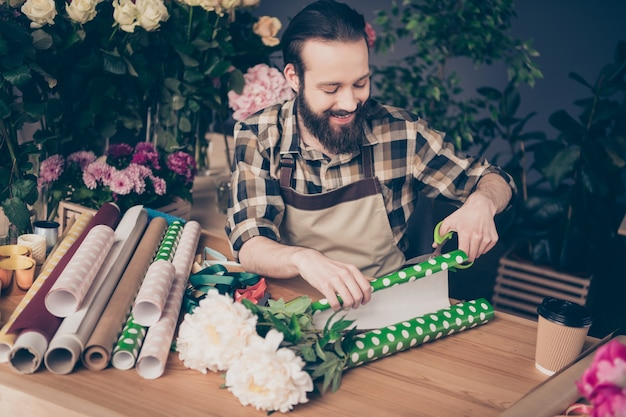 Bärtiger florist, der in seinem blumenladen arbeitet