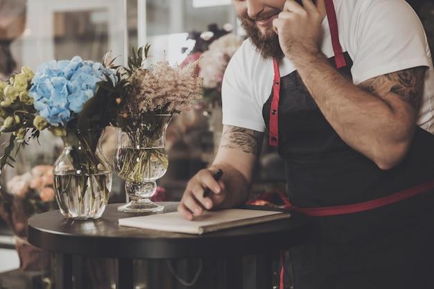 Bärtiger florist nimmt eine bestellung per handy entgegen