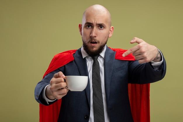 Bärtiger geschäftsmann des superhelden im roten umhang, der tasse kaffee hält, der mit zeigefinger darauf zeigt, verwirrt über hellgrüner wand stehend
