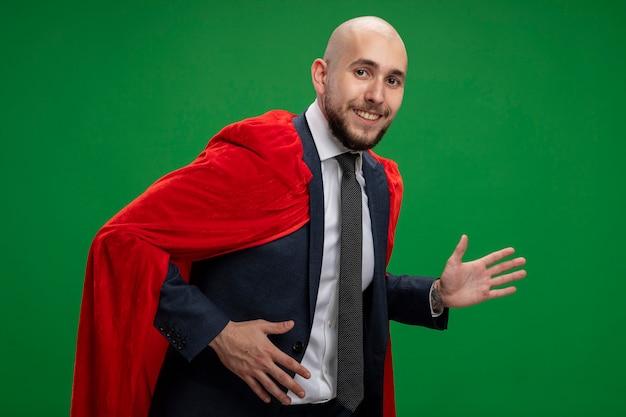 Bärtiger geschäftsmann des superhelden im roten umhang, der über grüner wand geht
