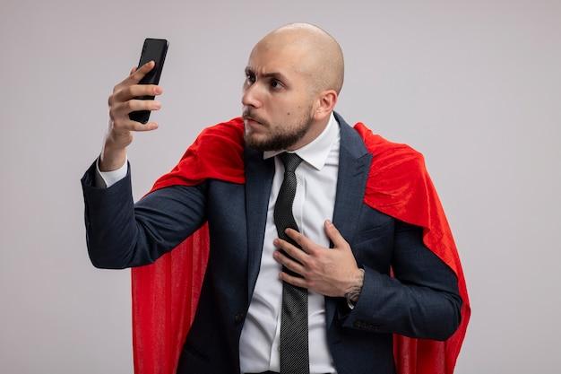 Bärtiger geschäftsmann des superhelden im roten umhang unter verwendung des smartphones, das es mit ernstem gesicht betrachtet, das besorgt über weißer wand steht