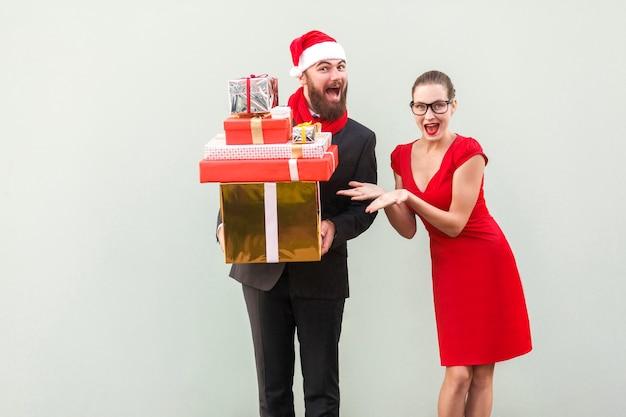 Bärtiger geschäftsmann hält viele geschenkboxen, frau zeigt seine hände auf der box. glück und lustige gut gekleidete paare, die kamera, offenen mund und zahniges lächeln betrachten. studioaufnahme, grauer hintergrund