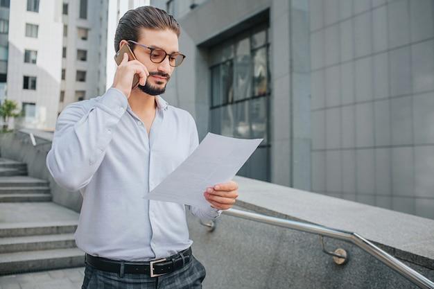 Bärtiger geschäftsmann mit sonnenbrille steht auf stufen und hält ein stück papier. er sieht sich das dokument an. guy studiert es. gleichzeitig telefoniert er.