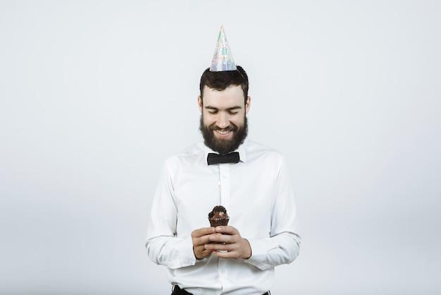 Bärtiger glücklicher mann in einer kappe hält einen kuchen mit einer kerze in seinen händen auf grau