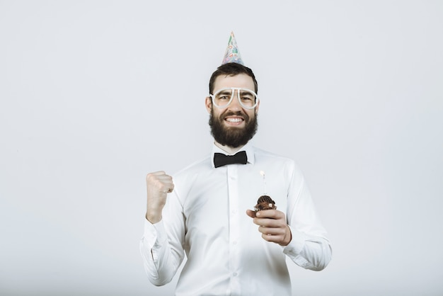 Bärtiger glücklicher mann in einer partykappe und in den gläsern hält einen kuchen mit einer kerze in seinen händen auf grau