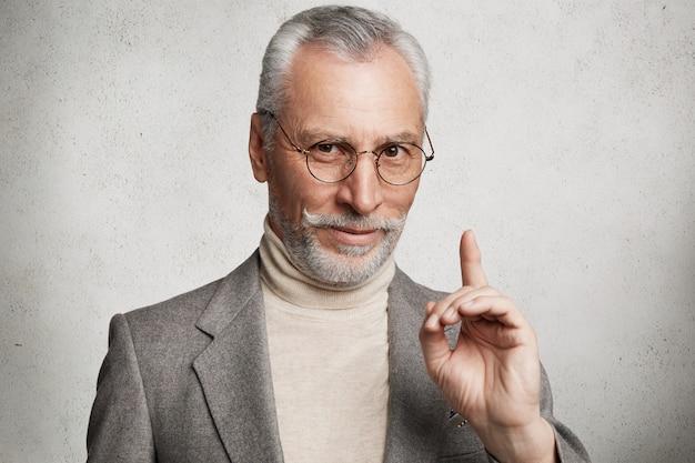 Bärtiger grauhaariger älterer mann, der formellen anzug trägt