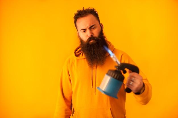 Bärtiger handlicher mann, der lötlampe über gelbem hintergrund hält. professionelles werkzeug. blaues werkzeug