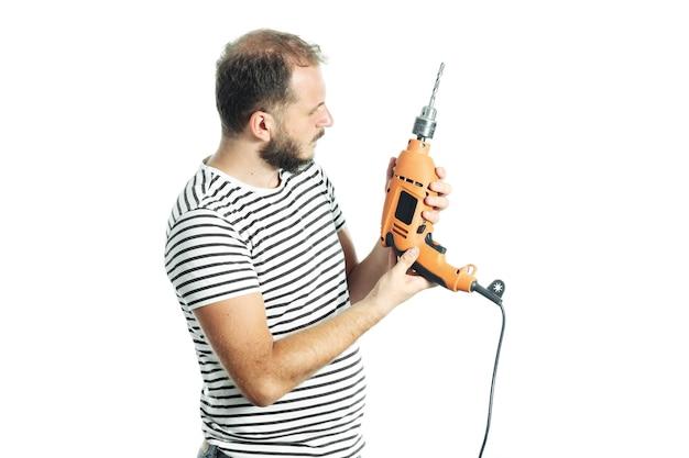 Bärtiger handwerker im gestreiften t-shirt, der mit fragendem blick auf die bohrmaschine in der hand schaut