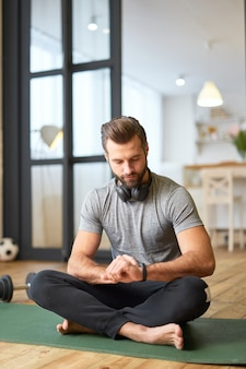 Bärtiger herr mit kabellosen kopfhörern um den hals, der auf einer yogamatte sitzt und auf eine moderne uhr an seiner hand schaut