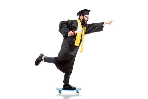 Bärtiger hipster-absolvent, der ein skateboard reitet, nach vorne zeigt und diplom hält, isoliert