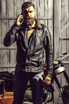 Bärtiger hipster-biker mit bart und schnurrbart in lederjacke und sonnenbrille in der nähe von motorrad mit weinflasche und handy auf holzhintergrund