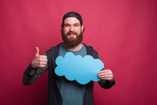 Bärtiger hipster hält eine blaue wolke und zeigt daumen hoch geste