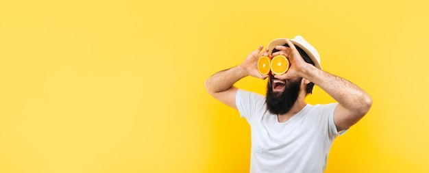 Bärtiger hipster-mann, der orange scheiben vor augen hält
