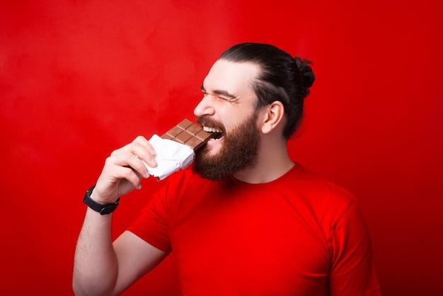 Bärtiger hipster-mann, der schmackhafte tafel schokolade über roter wand isst