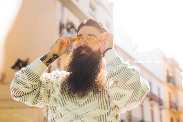 Bärtiger hübscher junger mann, der auf die gelbe sonnenbrille während des sommers sich setzt