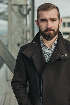 Bärtiger hübscher junger mann vor brückenbau mit flirt und leichtem lächeln. er trägt eine braune jacke und ein leichtes hemd.
