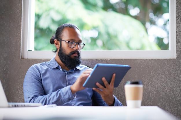 Bärtiger indischer mann in den gläsern, die am schreibtisch im büro sitzen und tablette verwenden