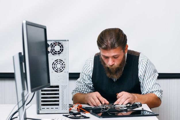 Bärtiger ingenieur, der computer am arbeitsplatz zusammenbaut. reparaturmann, der computer innerhalb des stromkreises im büro repariert. elektronische renovierung, technologie, geschäftskonzept