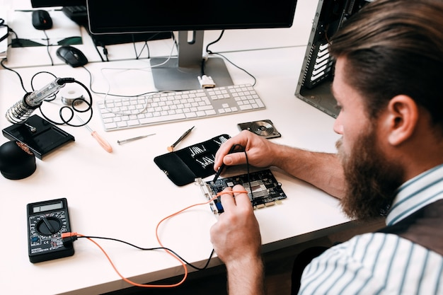 Bärtiger ingenieur testet mikroschaltung. arbeitsplatz des ingenieurs, der elektronik in der reparaturwerkstatt repariert