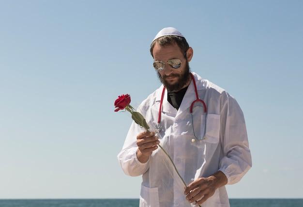 Bärtiger jüdischer arzt in weißer yarmulke (hut, kippah, jüdischer hut) mit sonnenbrille, mantel und stethoskop, die rote rosenblume in der hand hält. amerikanischer gutaussehender bärtiger mann senkte den kopf