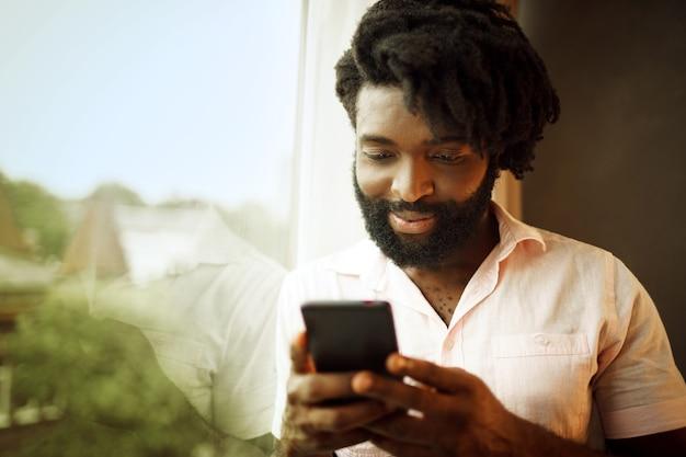 Bärtiger junger afroamerikanermann, der sein smartphone betrachtet