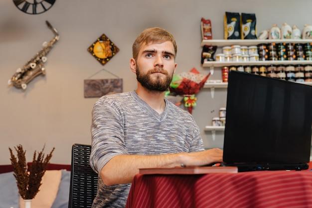 Bärtiger junger erwachsener mann arbeitet an einem laptop in einem café, während er an einem tisch sitzt.